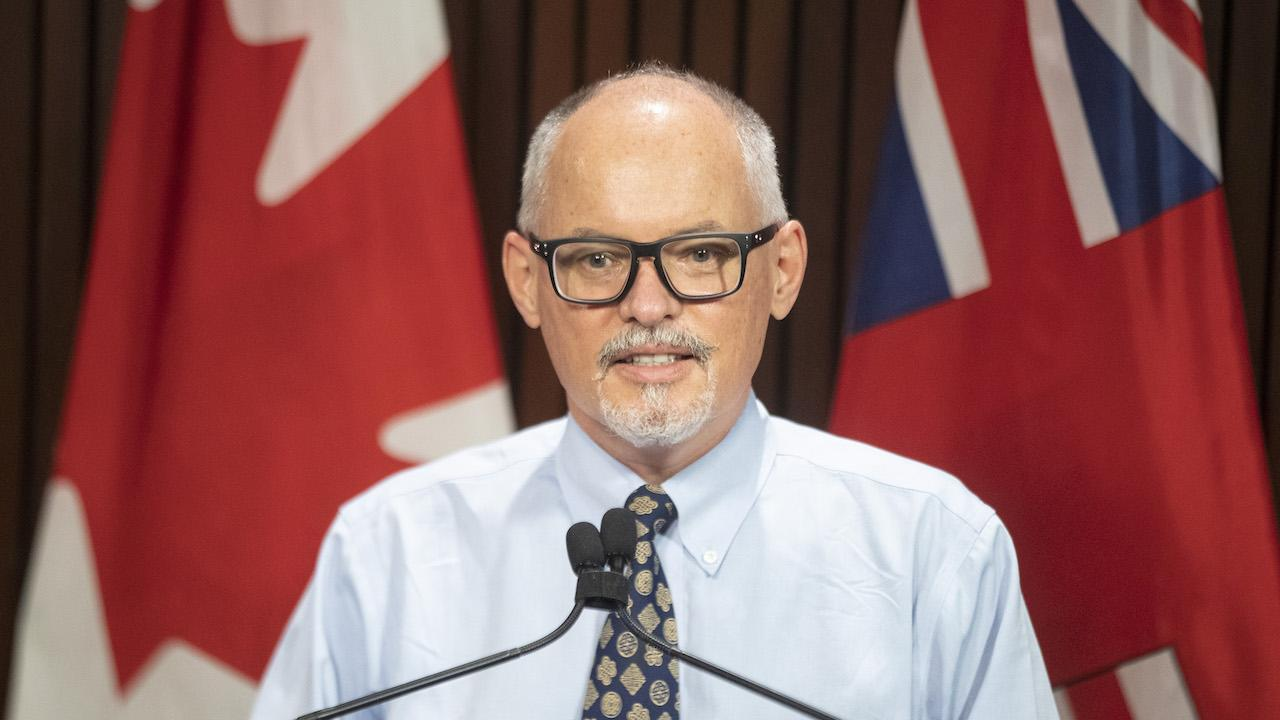 man in tie and glasses stands behind microphones and in front of flags