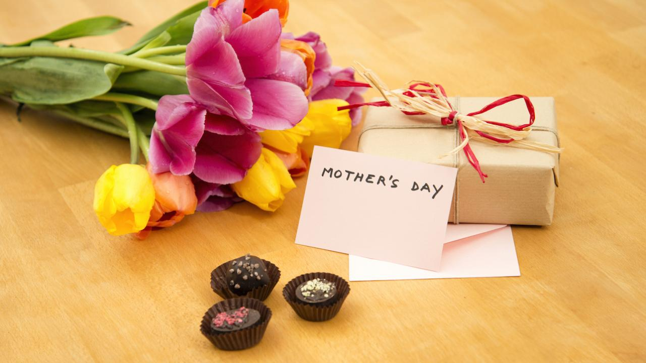 """pink and yellow flowers, chocolates, a present, and a card reading """"Mother's Day"""""""