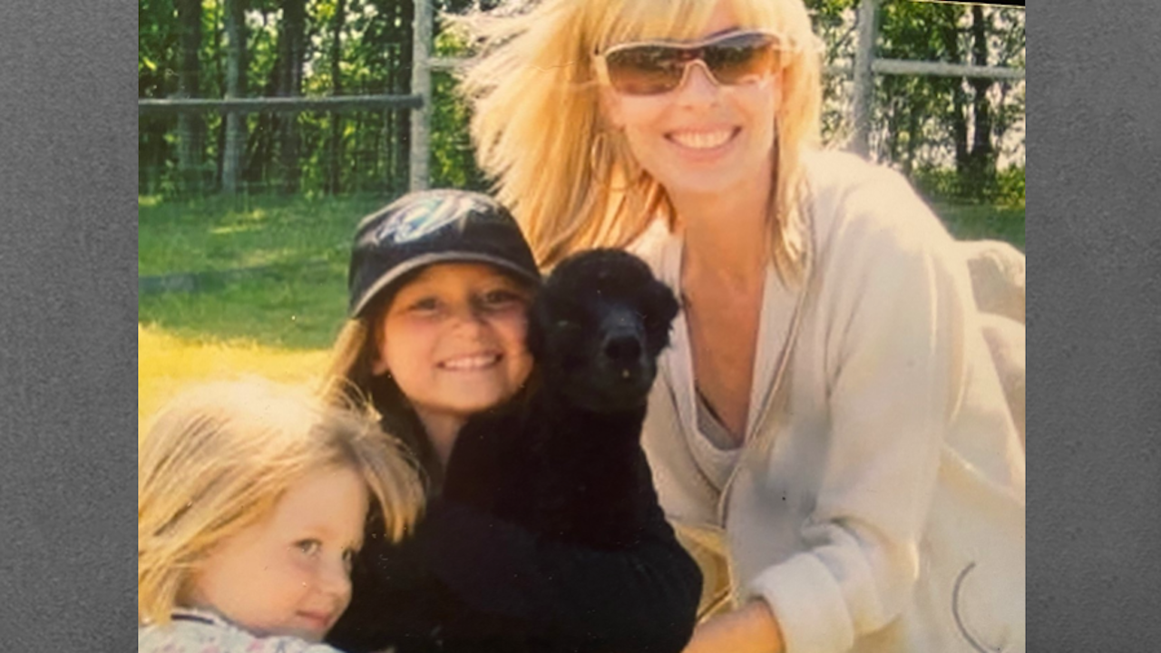 a woman in sunglasses with two children and a dog