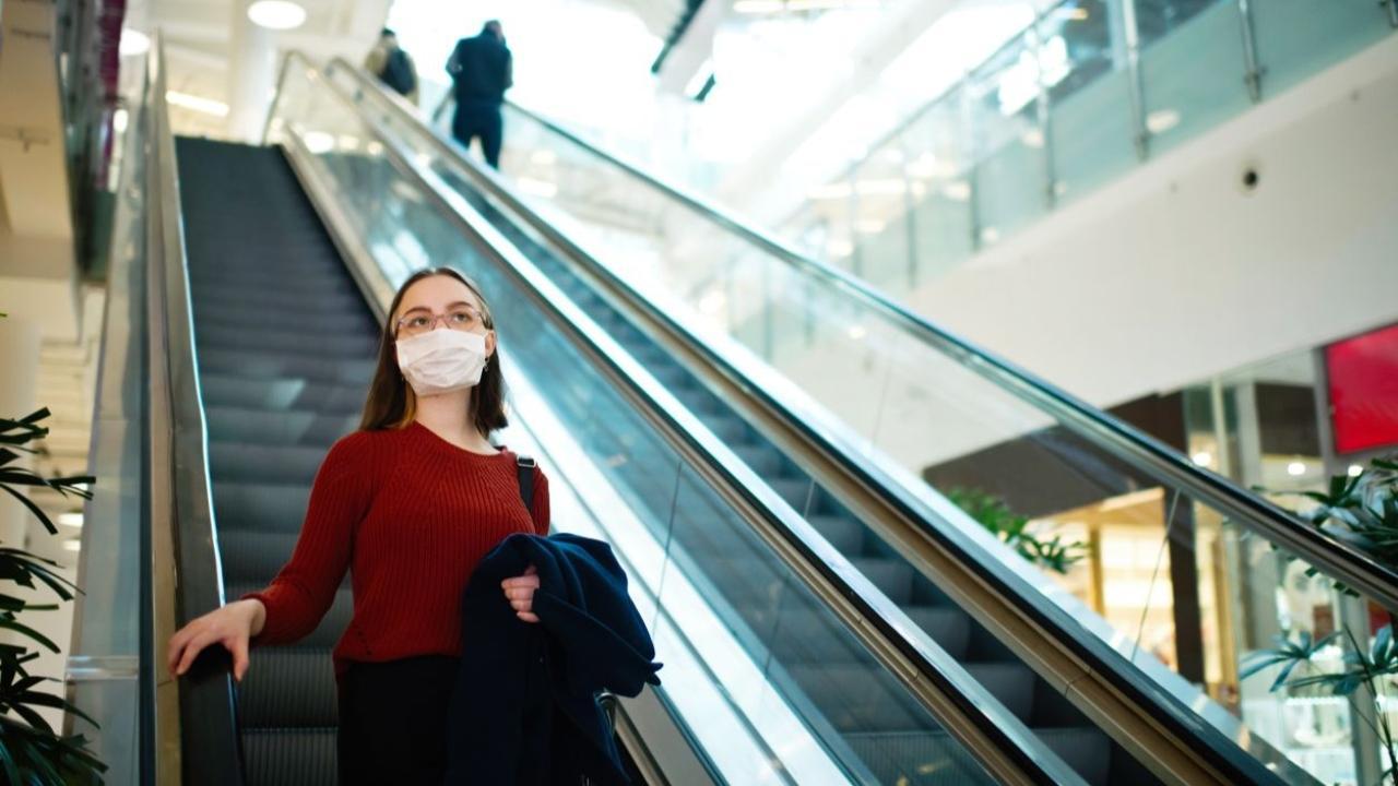 woman on escalator wearing mask
