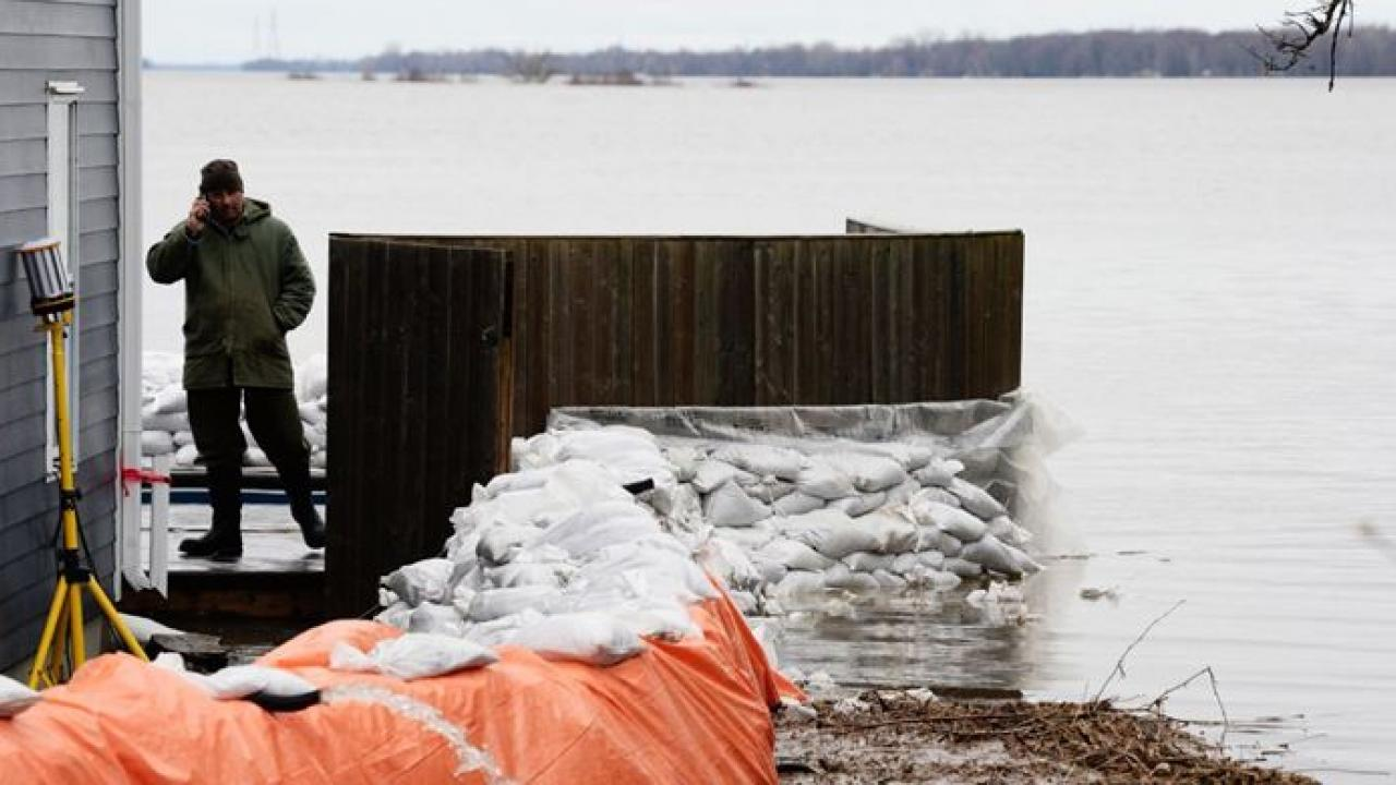 a man prepares for flooding in Rockland, Ont.