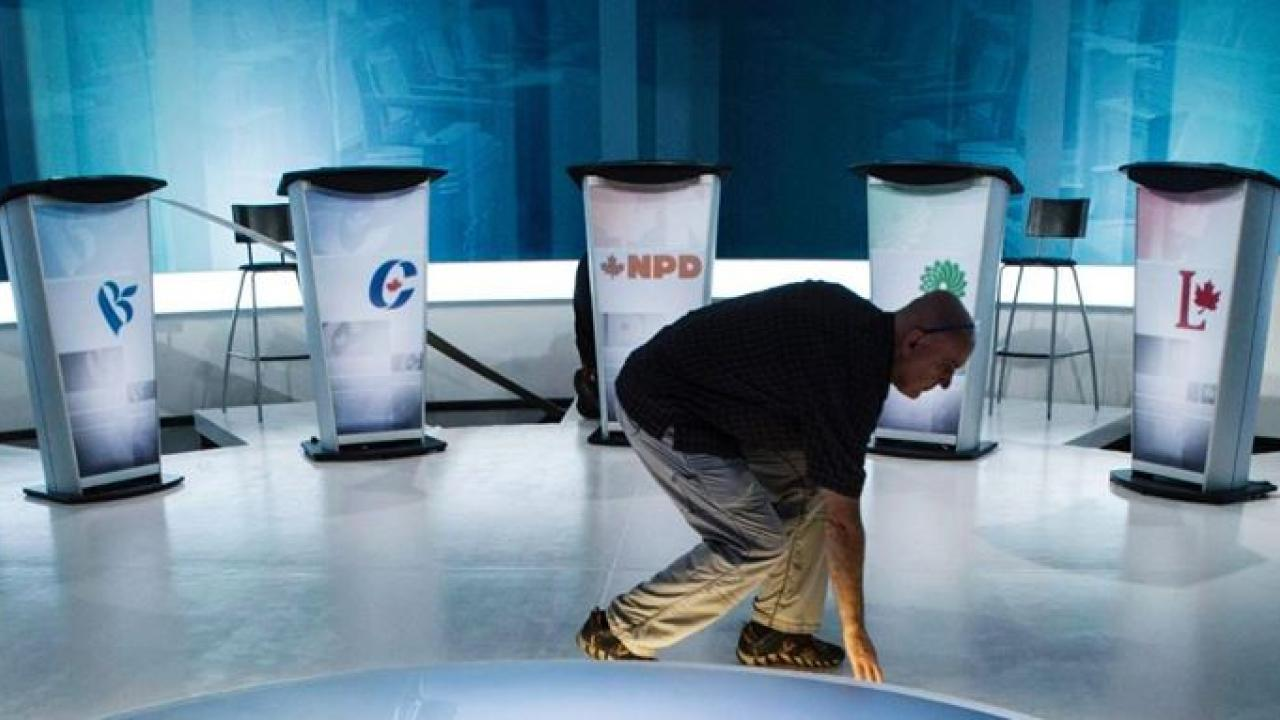 a person cleaning up a TV studio after a debate