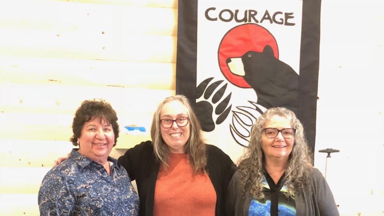 """three smiling women stand in front of a sign reading """"courage"""""""