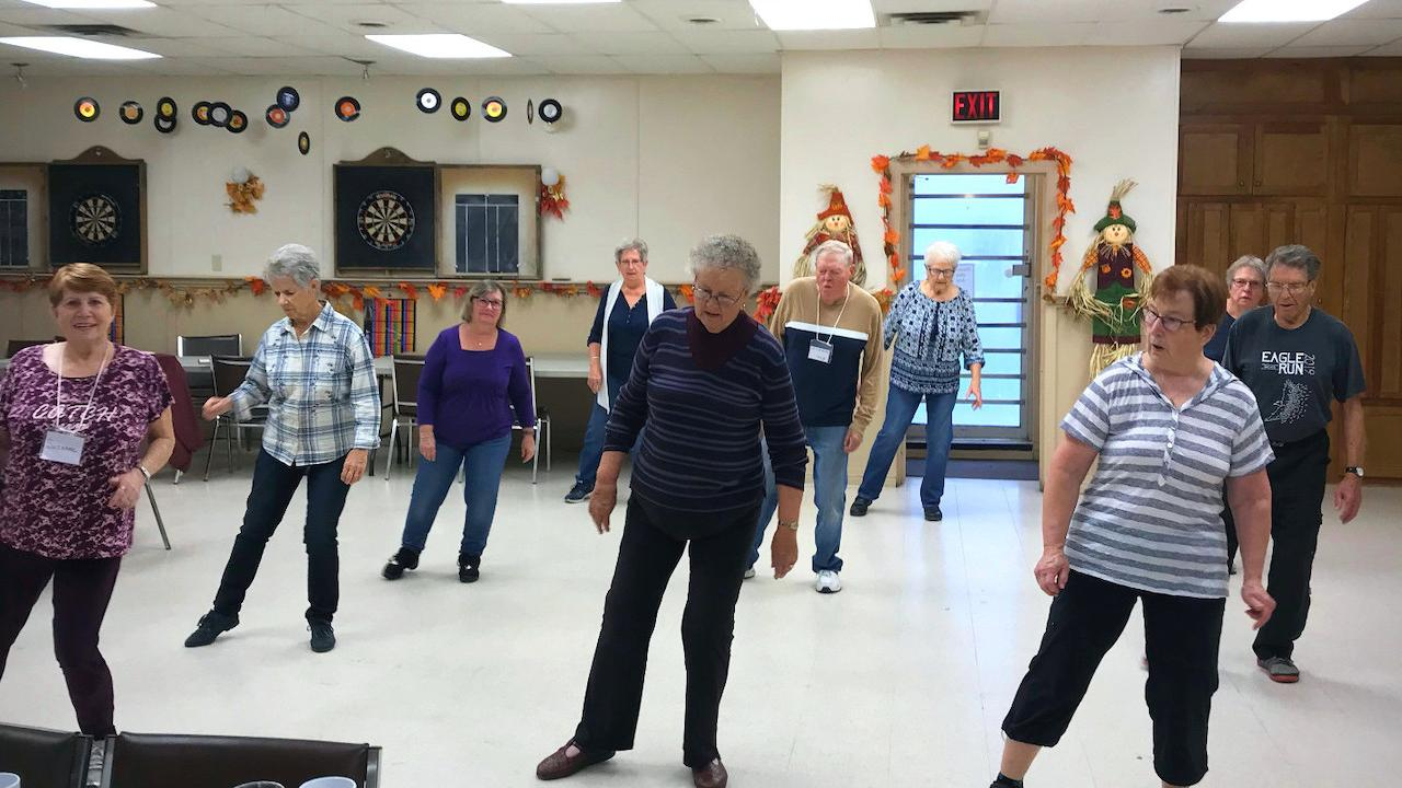 a group of older adults at a line-dancing class