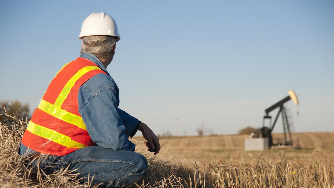 an oil worker sits while watching a derrick in a field