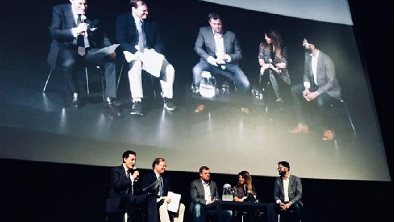 Five people sit on stage in front of large screen showing their image.
