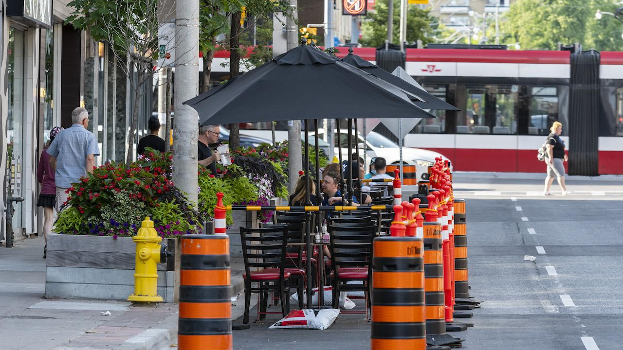 people eat at a table set up on on a street, behind orange pylons