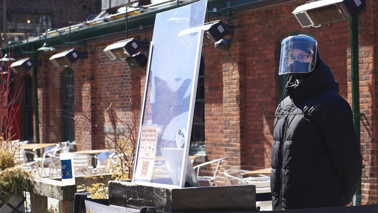 person in a face shield stands in front of a patio