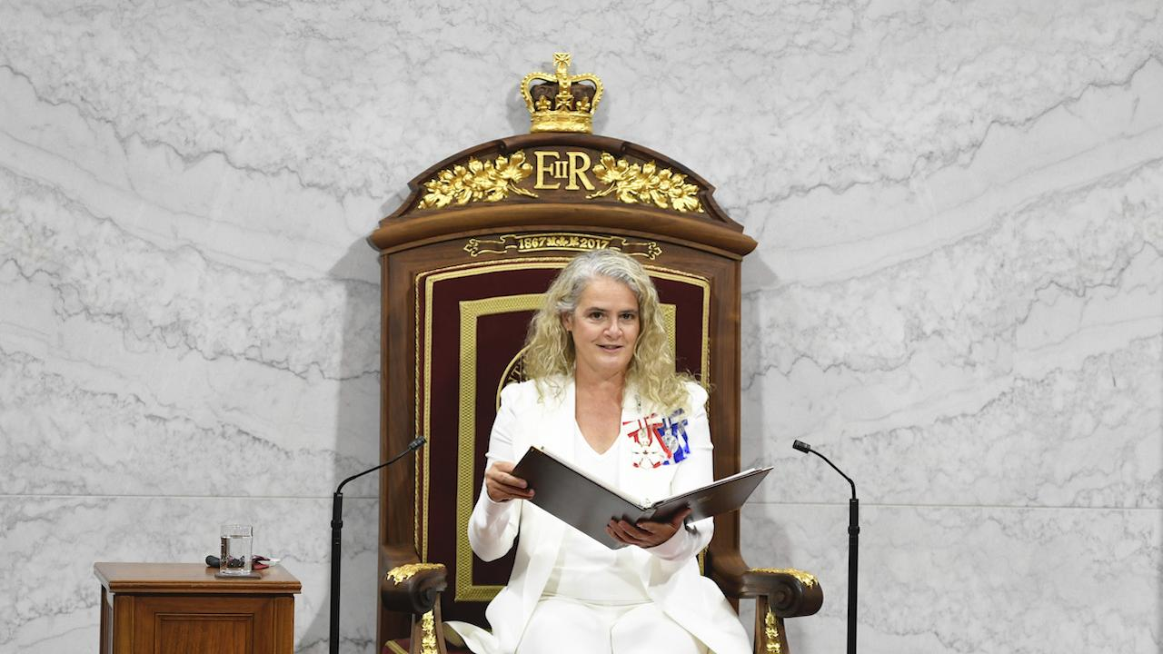 white-suited woman sits in a gilded chair holding a large book