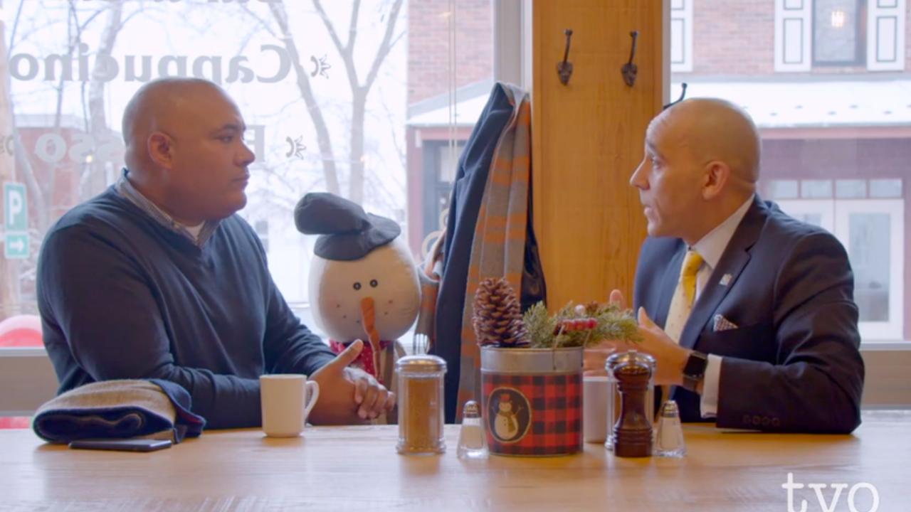 two men talking at a restaurant