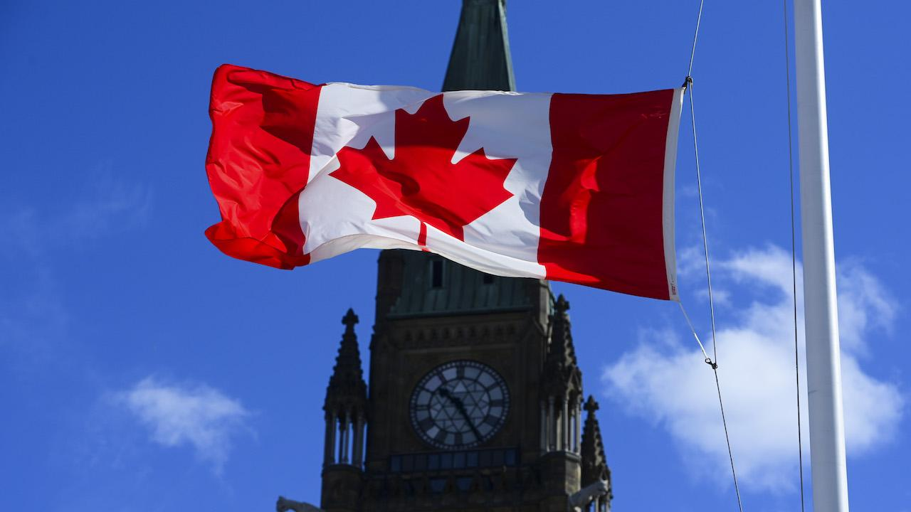 a Canadian flag flies into of a tower