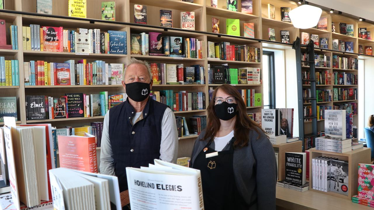 a masked man and woman stand in a bookstore