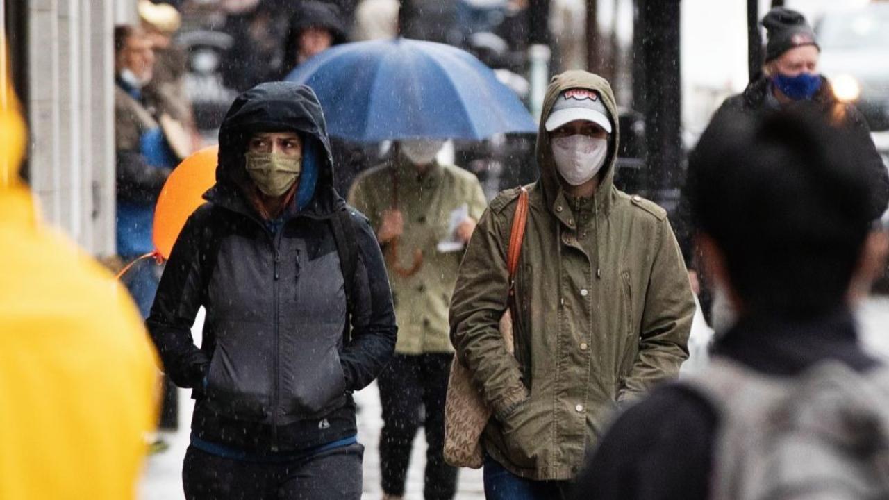 People walk on a crowded sidewalk wearing masks.