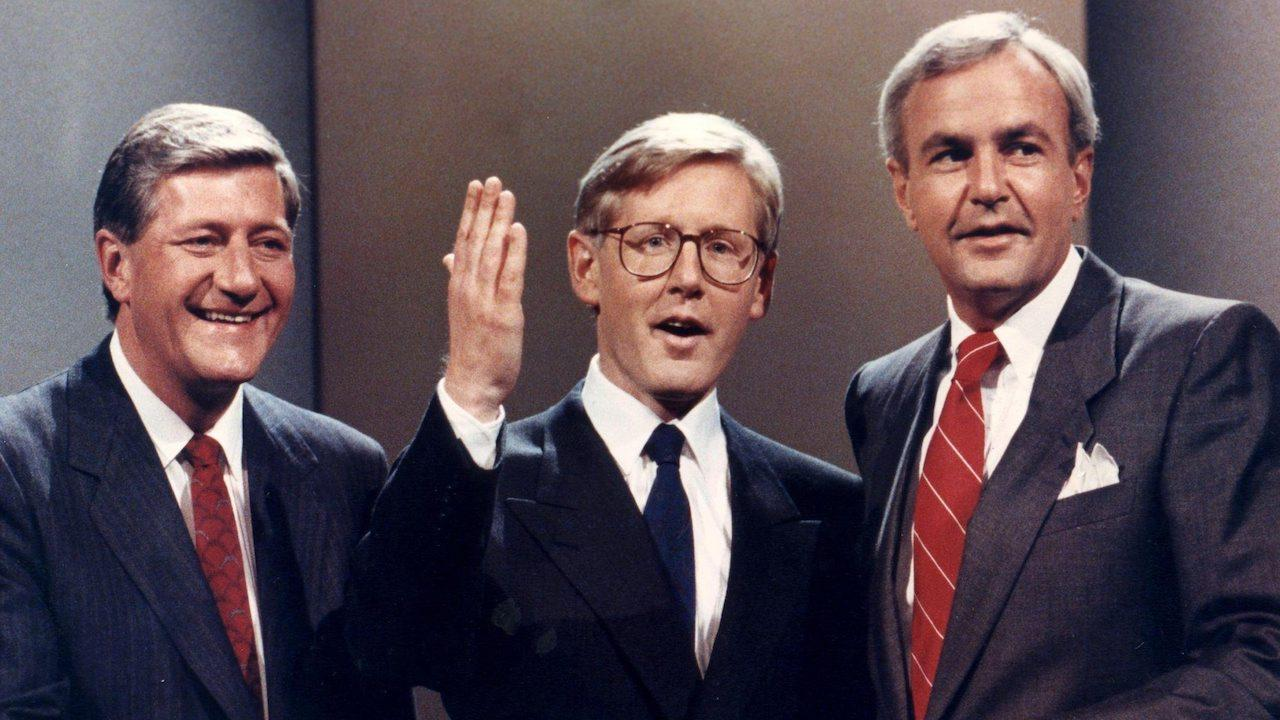 three smiling men in suits