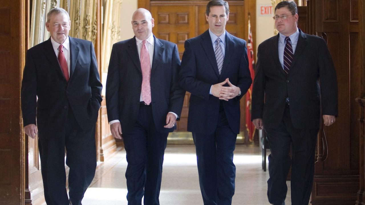 four men in suits walk down a hallway