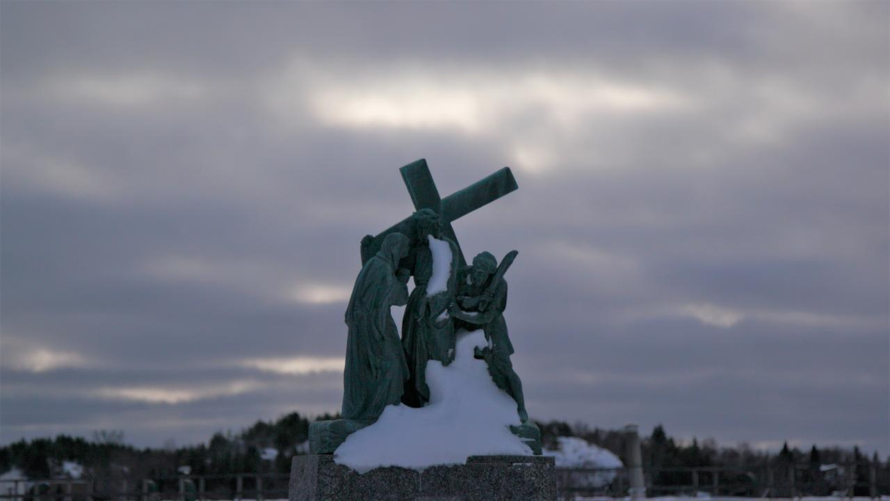 Statue of people holding up cross.