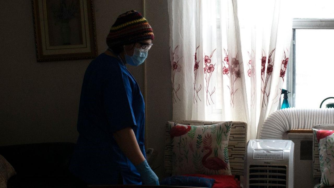 Person dressed in surgical mask and hospital scrubs.