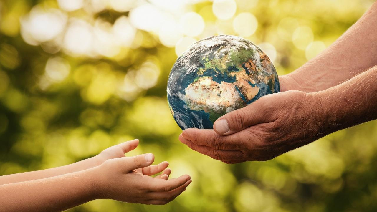 an adult handing the planet to a child