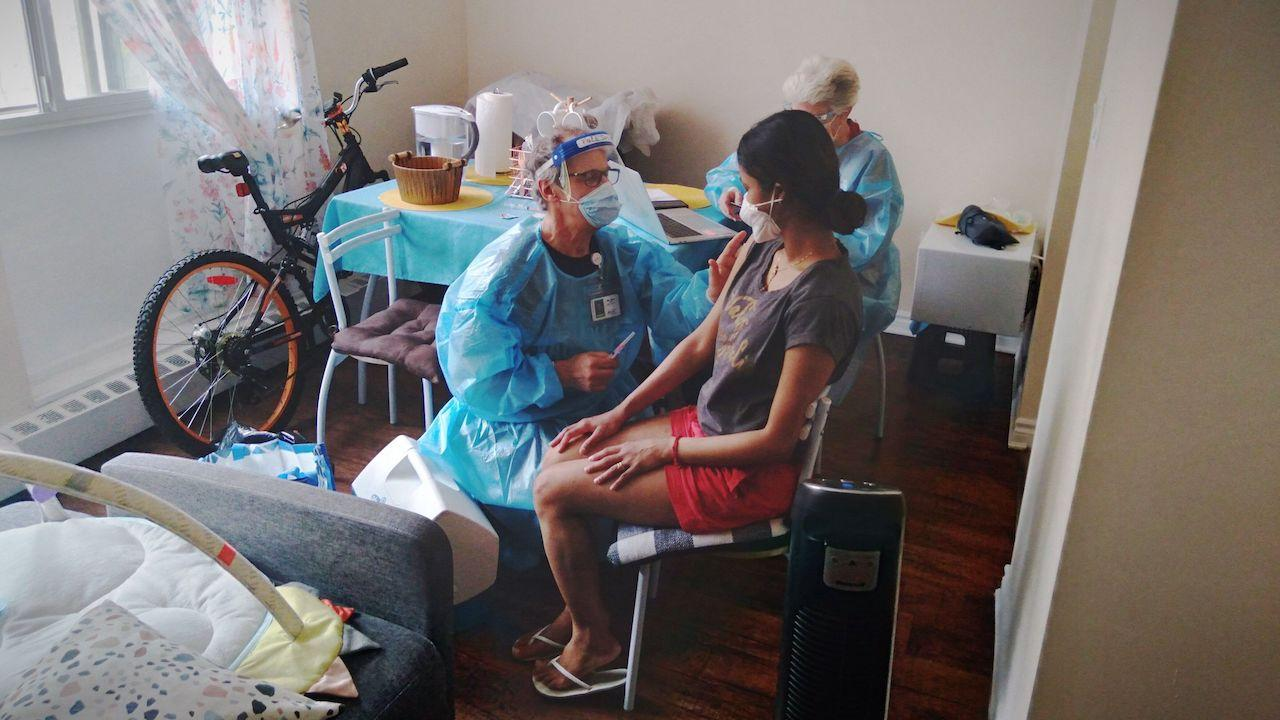 a masked woman sits on a chair while a man in PPE leans over her arm