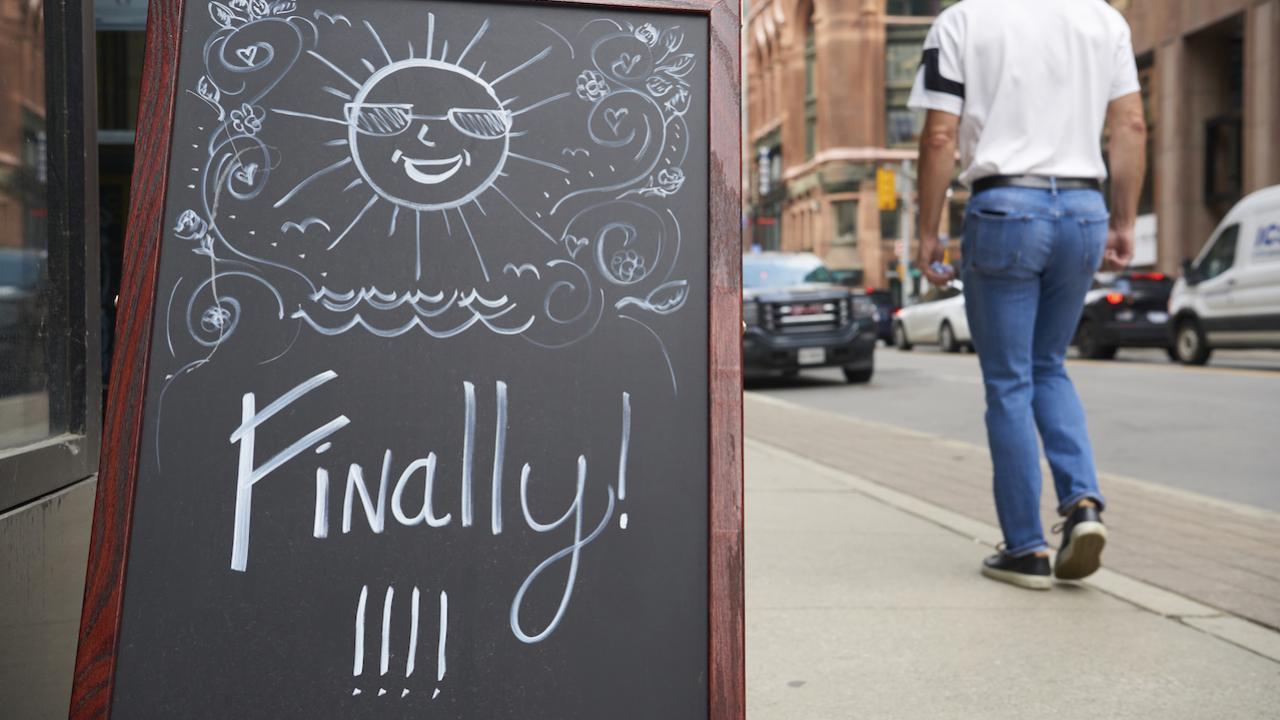 "man walks by restaurant sign reading ""finally!!!"""
