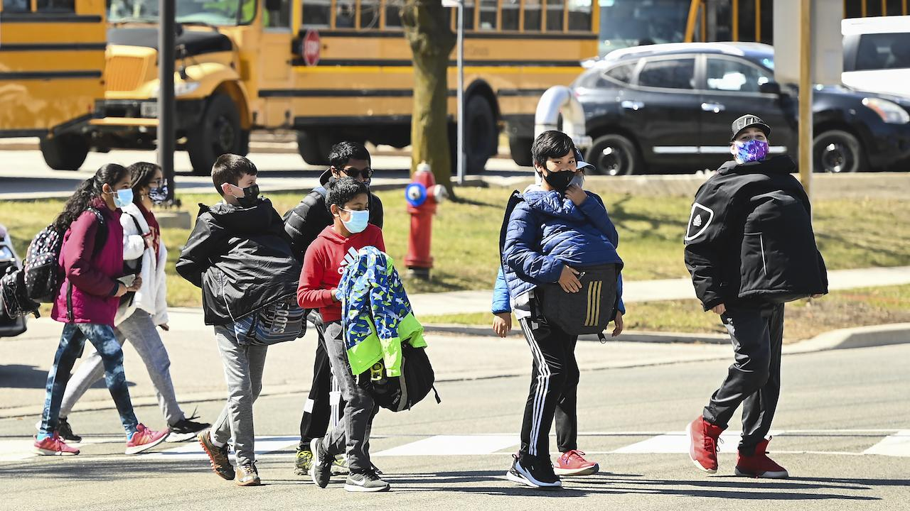 a group of children crossing the street in front of a school bus