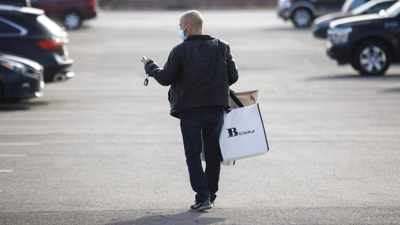 a masked man carries a shopping bag in a parking lot