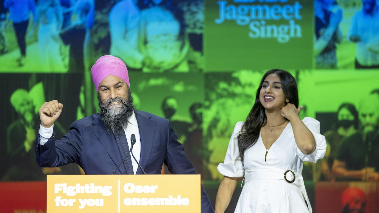 """man and woman in front of a sign reading """"Jagmeet Singh"""""""