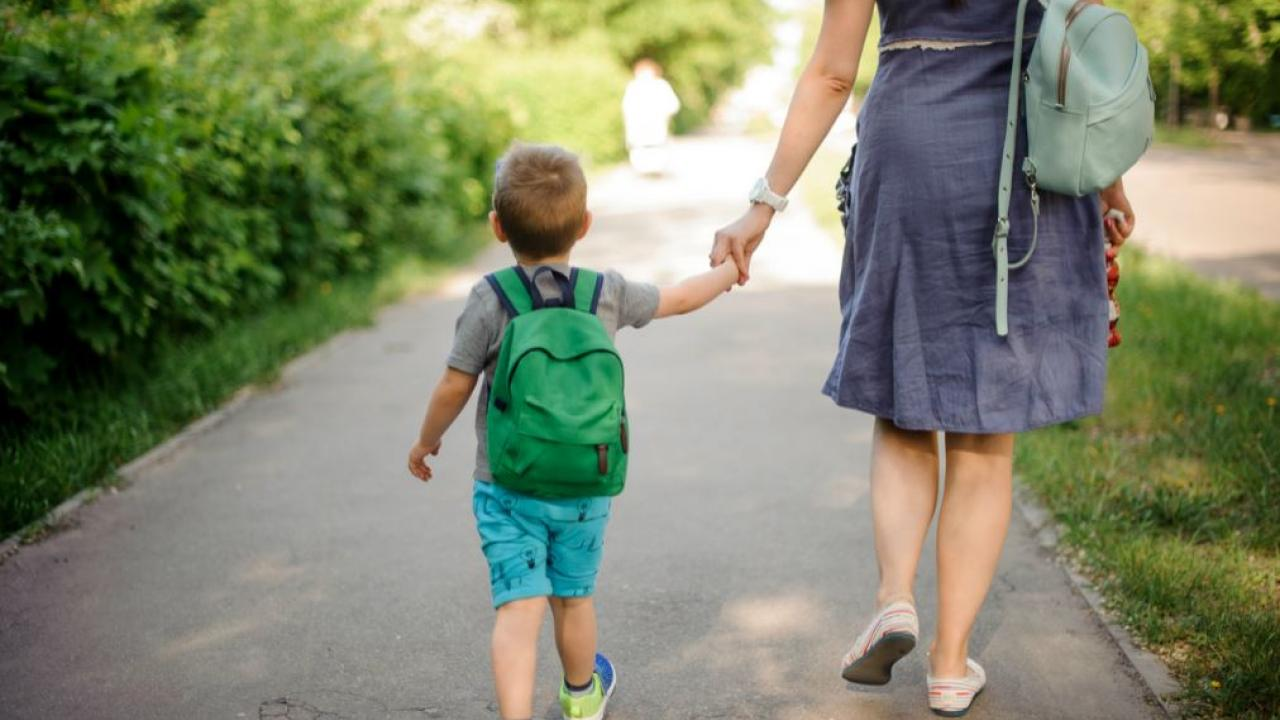 a child being walked to school by mother