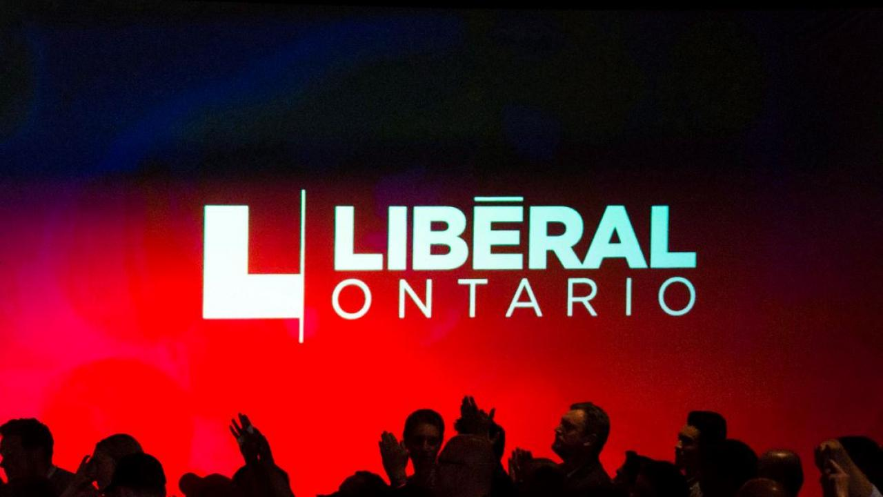 Silhouette of people standing in front of a sign that says Liberal Ontario