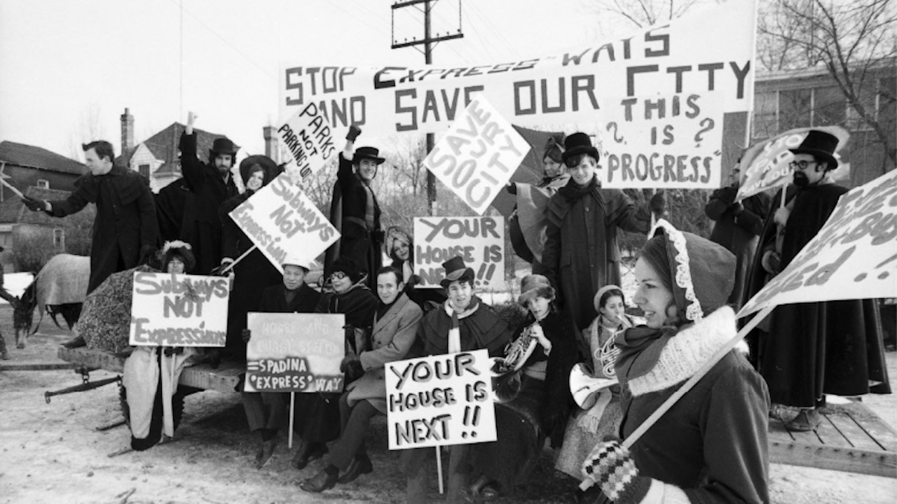 people dressed as pilgrims carrying signs