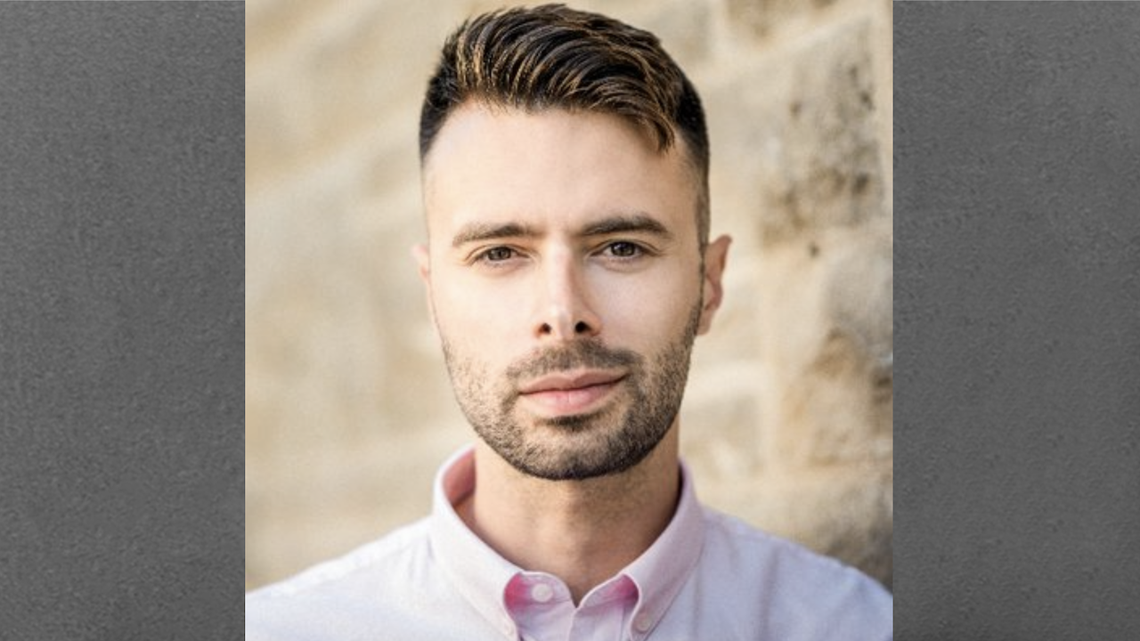 man with short hair in a pink collared shirt