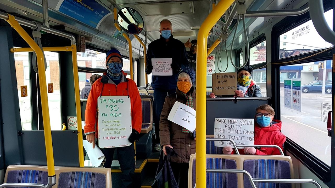 a group of people wearing masks and holding signs on a bus