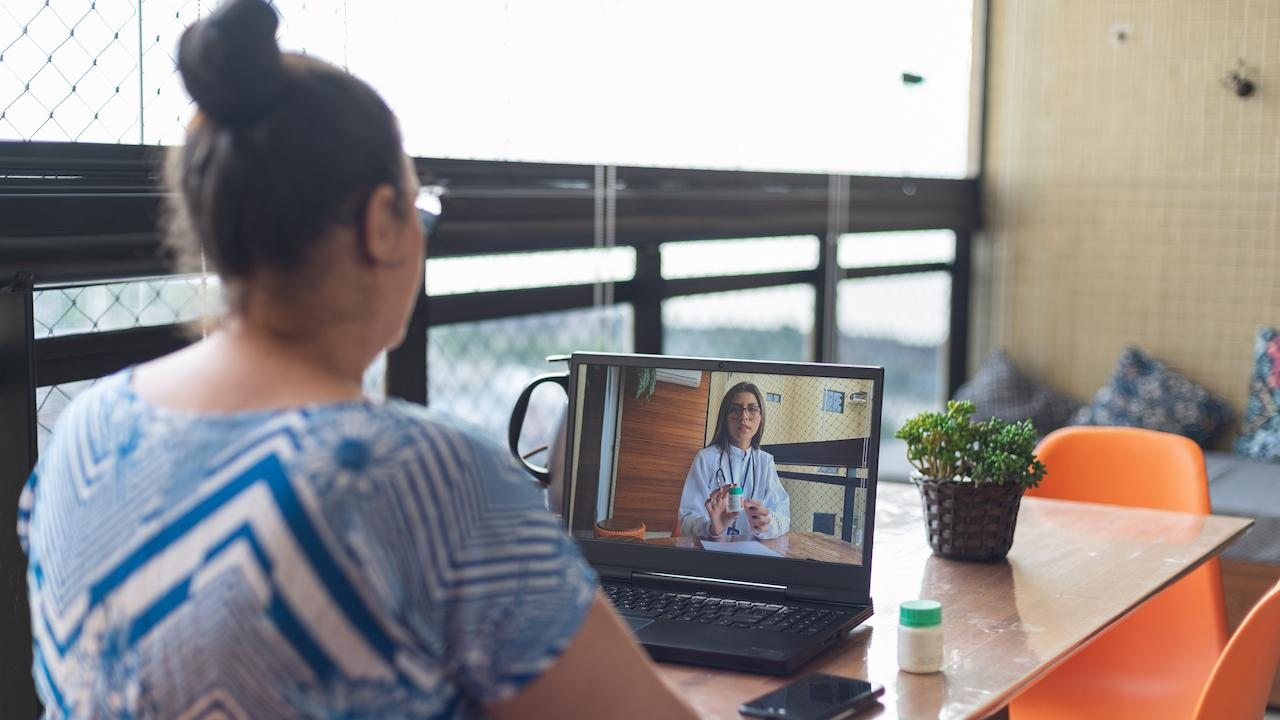 a woman video chatting with a therapist online