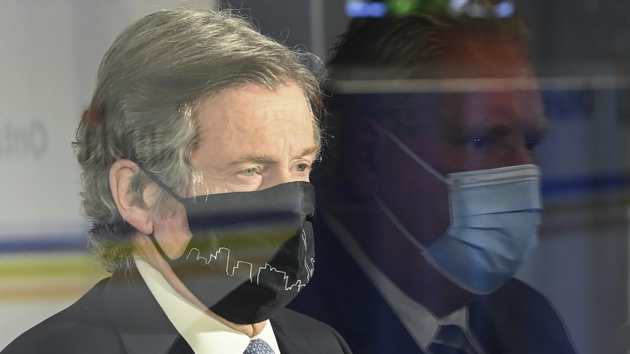 closeup of masked man beside the reflection of another masked man