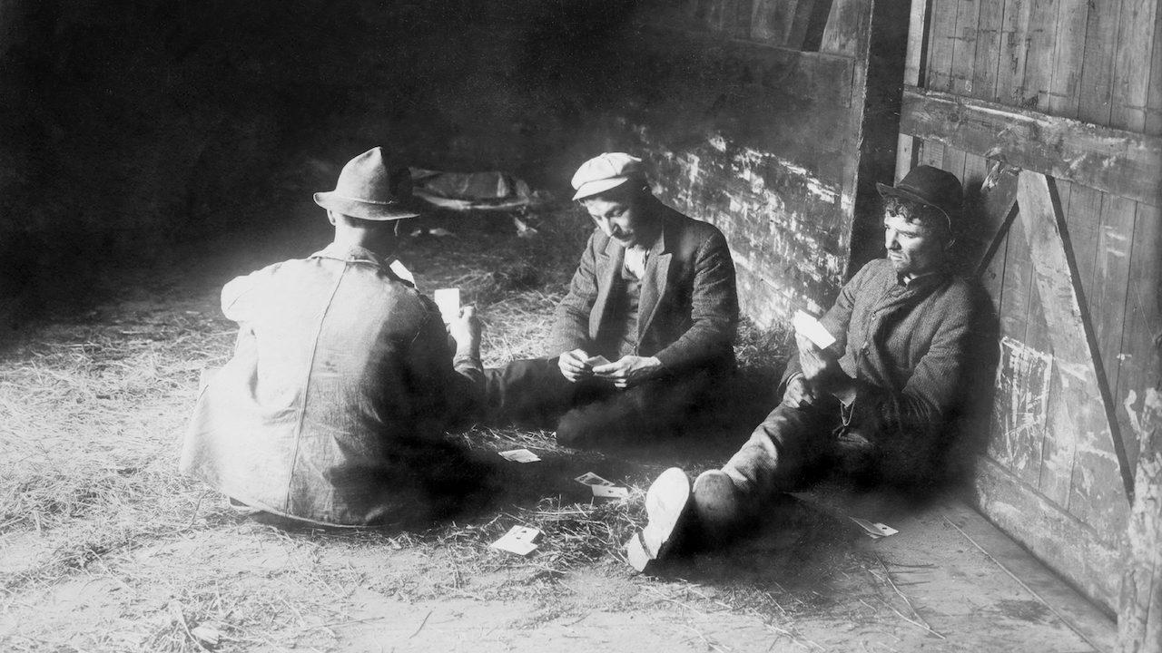 black and white photo of three men playing cards in a train car
