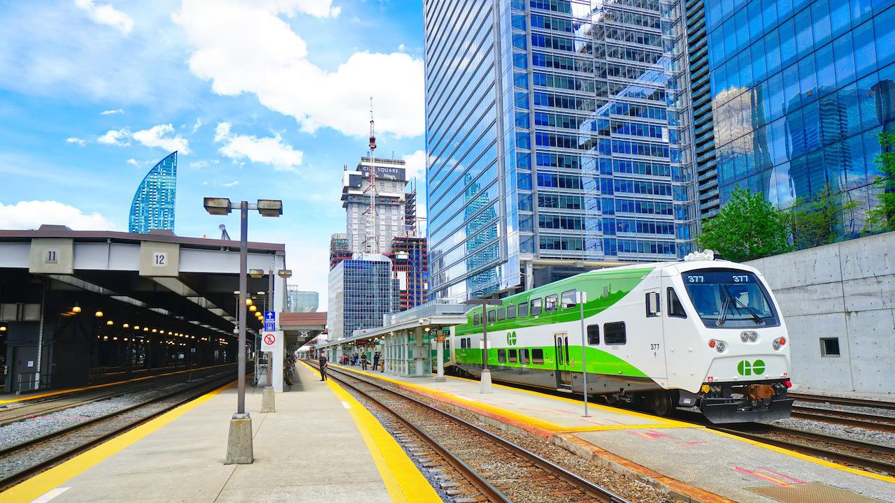 a green and white train in front of high-rises
