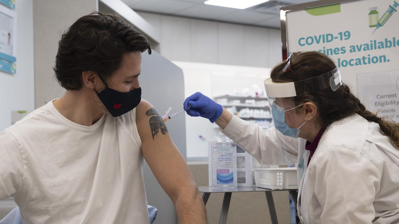 a masked man with a shoulder tattoo received a shot from a women in a face shield