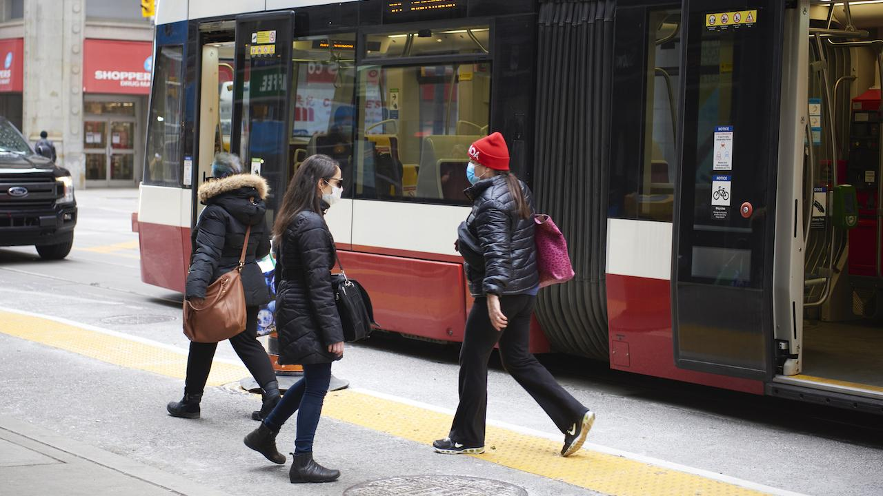 masked people walk in front of a streetcar