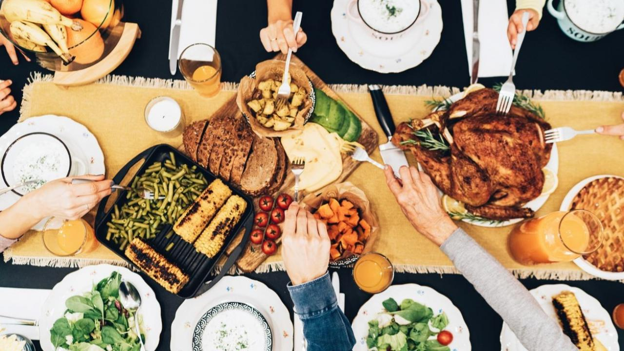 Overhead view of big family eating from table during a turkey dinner.