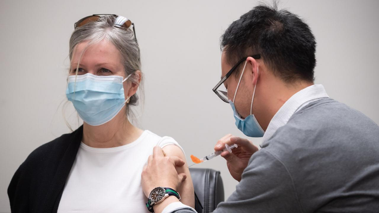 a masked woman in a white T-shirt gets a shot from a masked man in glasses
