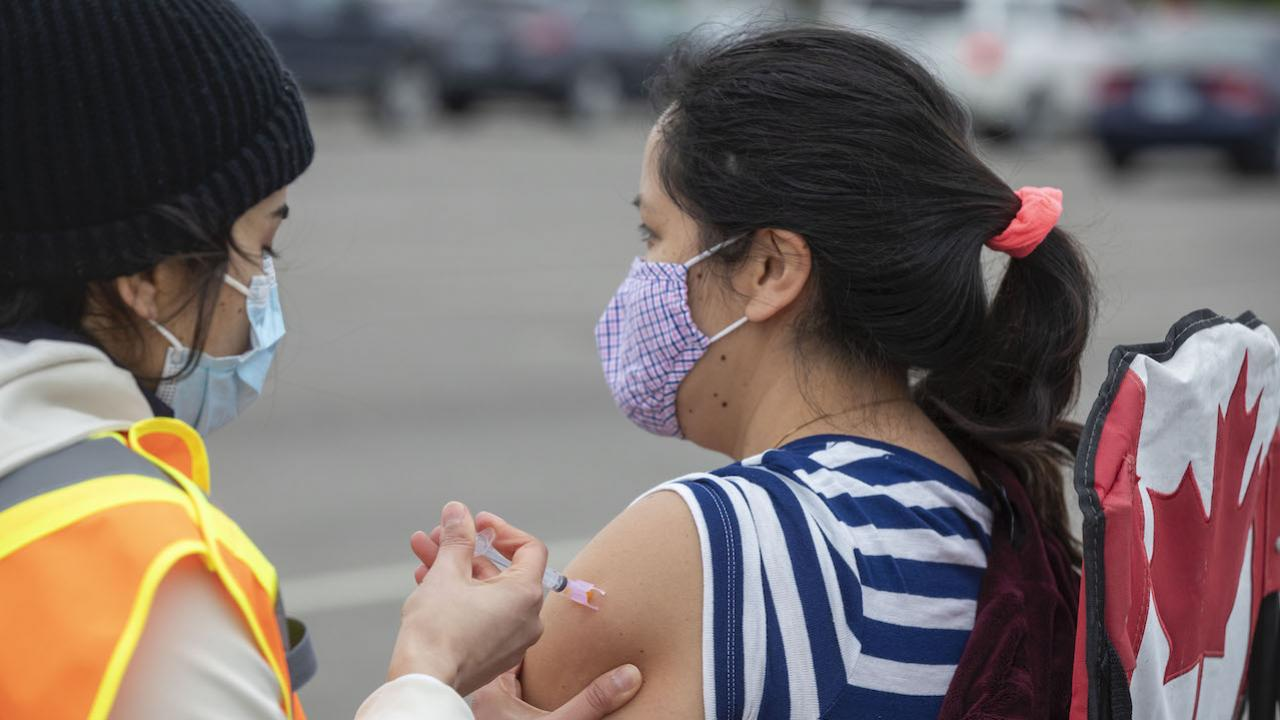 a woman in a striped shirt gets a shot from a masked woman