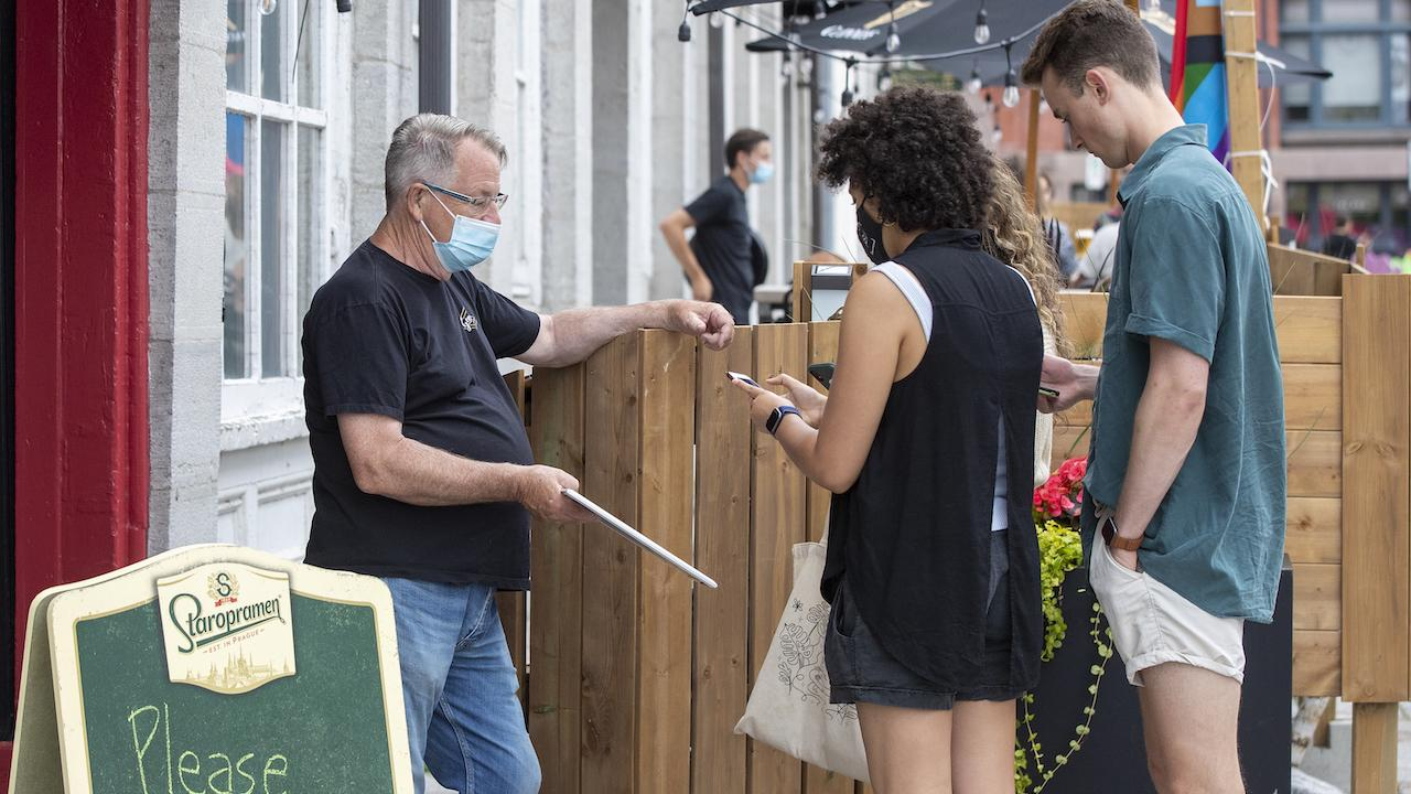 masked man in front of restaurant talks to a man and a woman