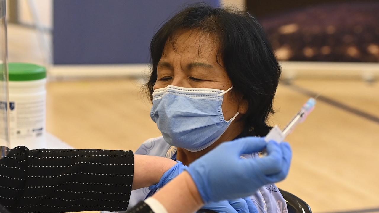 closeup of masked woman receiving a shot
