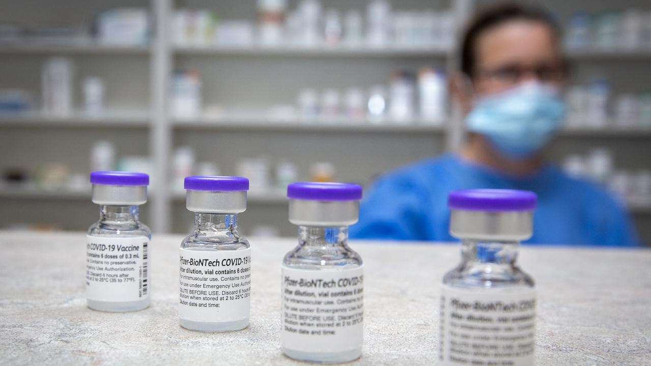 masked person blurry in background; vials of vaccine in foreground