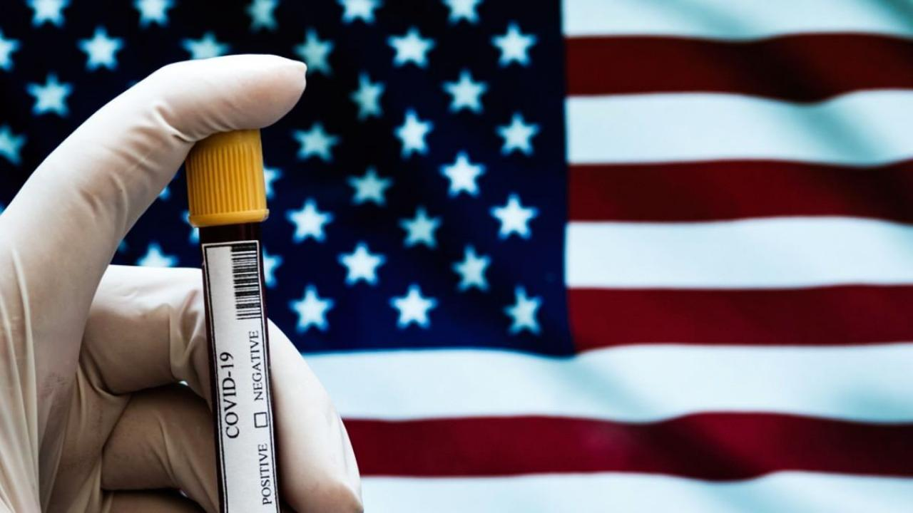Close-up of a Positive COVID-19 blood test sample with U.S. flag in background