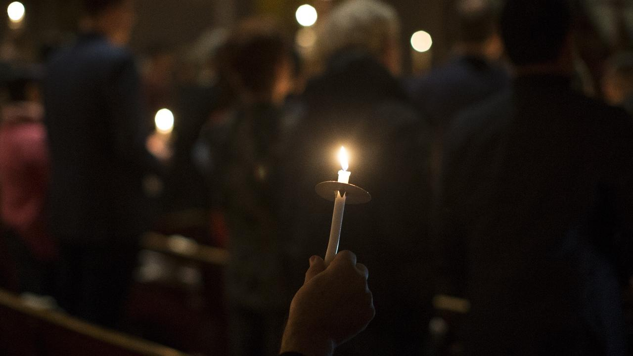people with candles holding a vigil