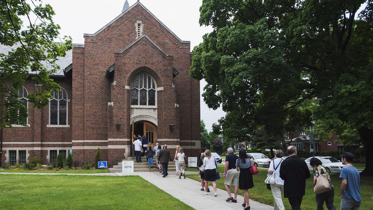 people in summer clothes line up outside a church