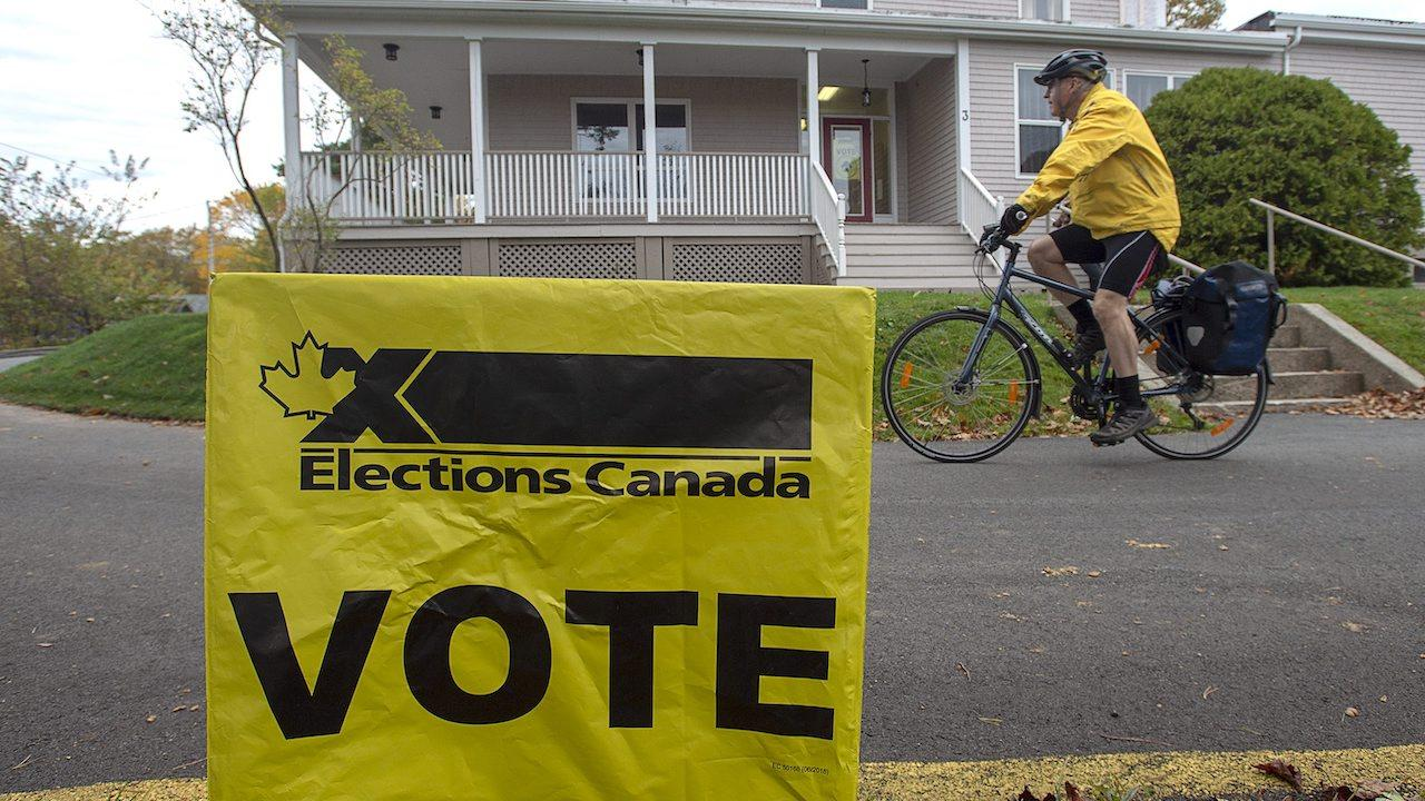 """cyclist rides past yellow Elections Canada """"vote """"sign"""
