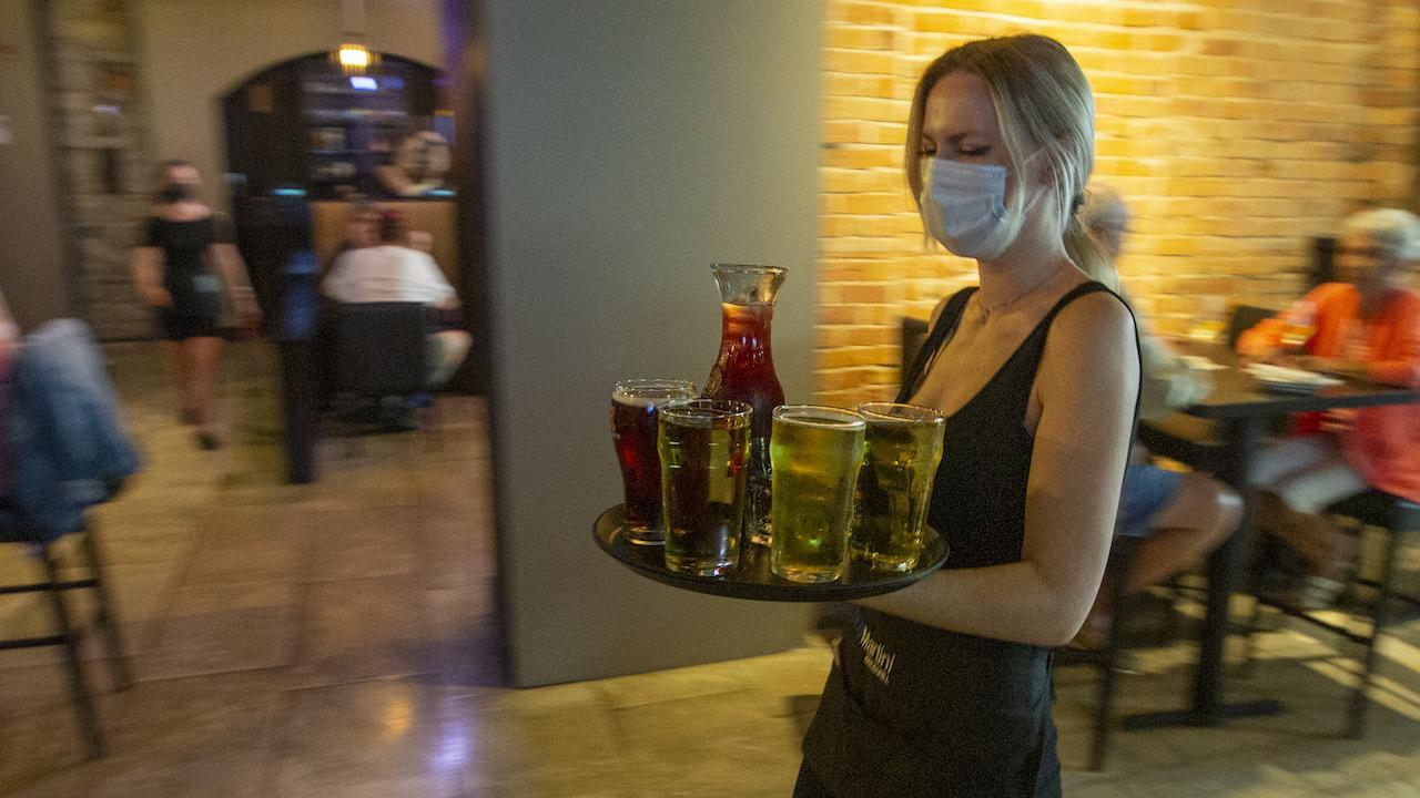 masked woman carrying a tray of drinks