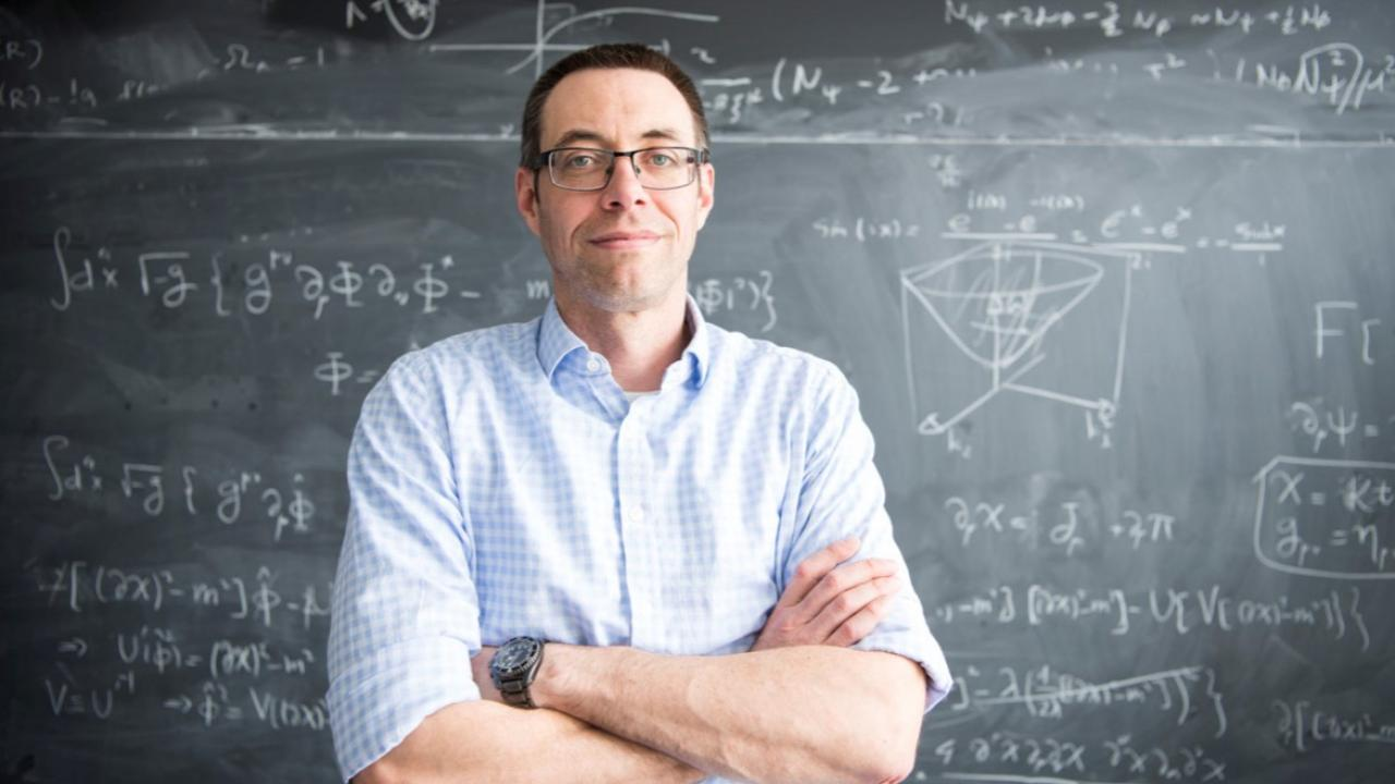 Man standing in front of blackboard with scientific equations written on it.